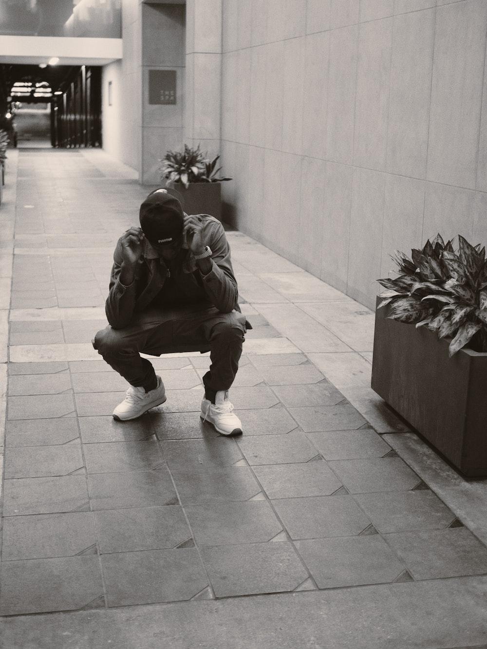 man in black jacket sitting on concrete bench