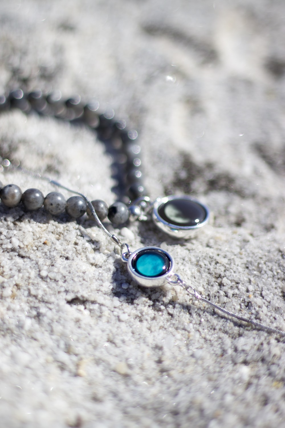 silver blue gemstone necklace on gray sand