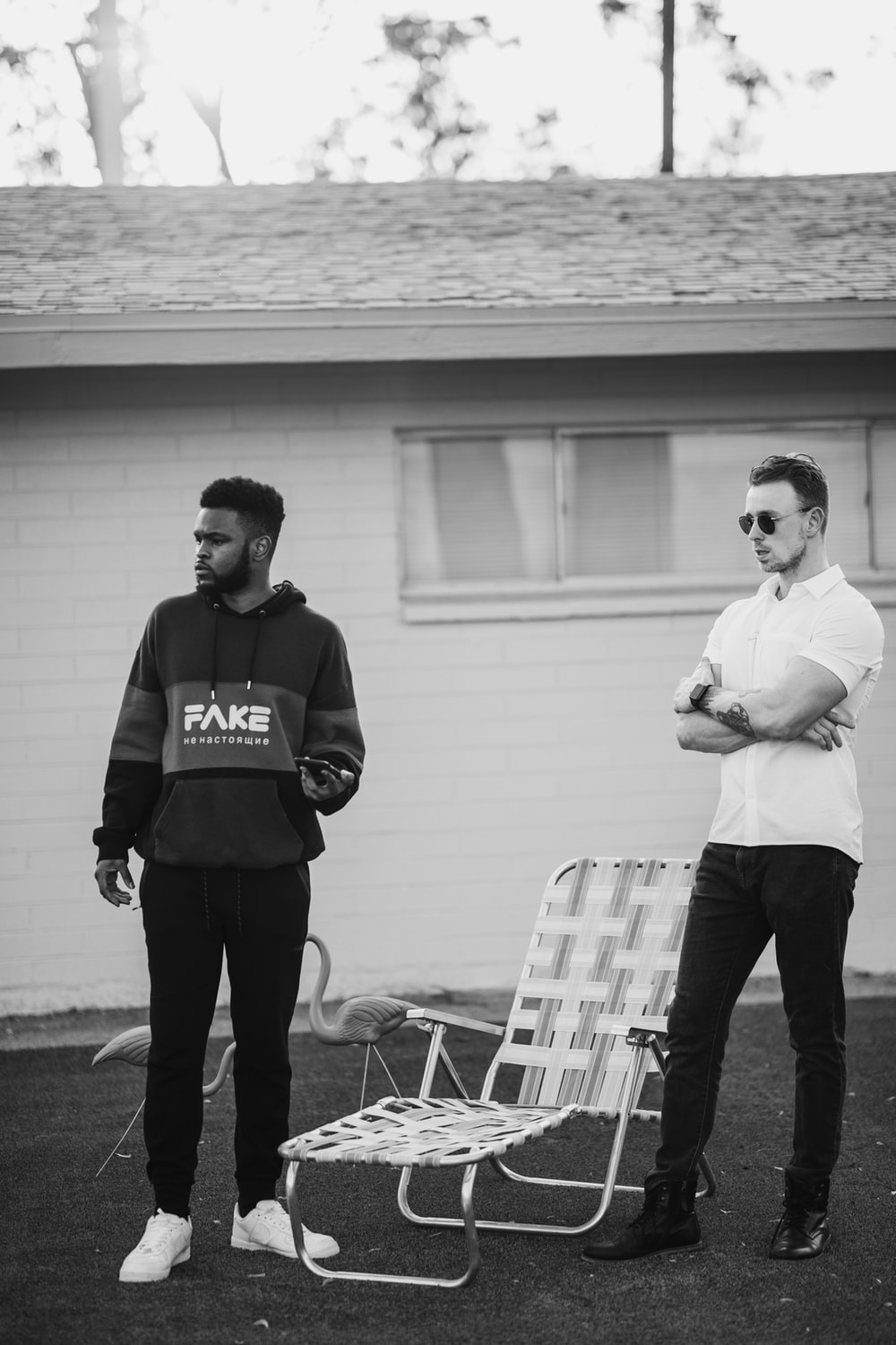 man in black and white hoodie standing beside man in white long sleeve shirt