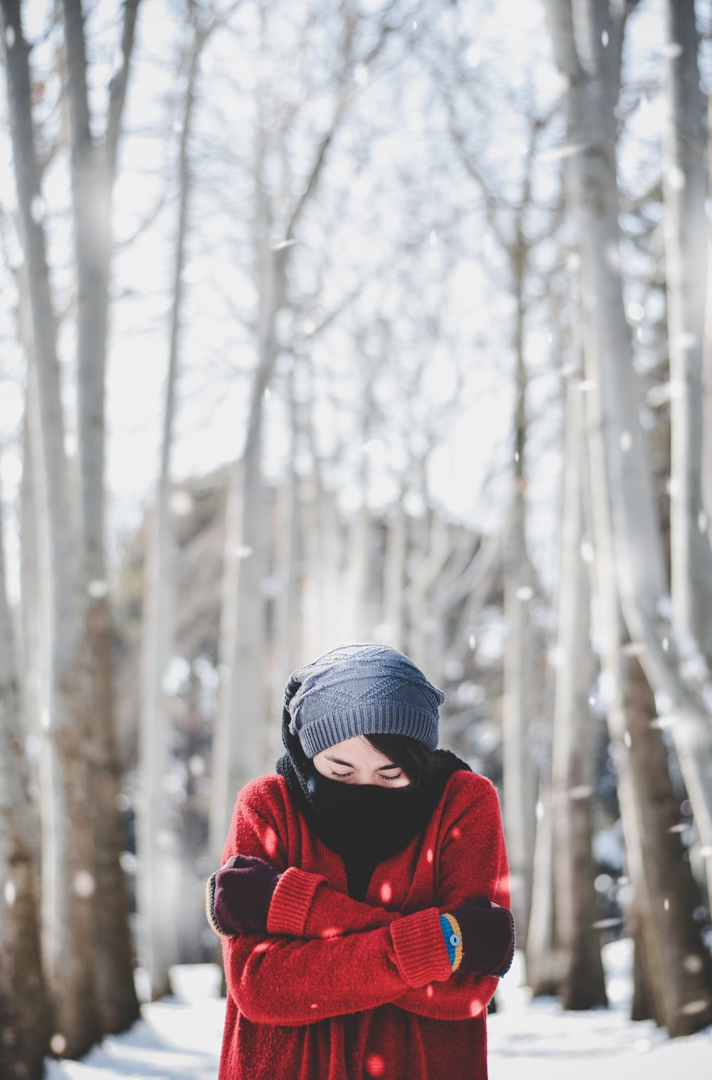person in red jacket wearing blue knit cap standing near snow covered trees during daytime