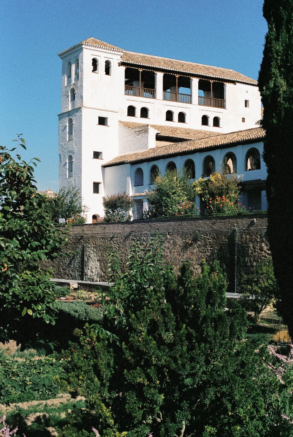 Edificio de hormigón blanco cerca de árboles verdes durante el día