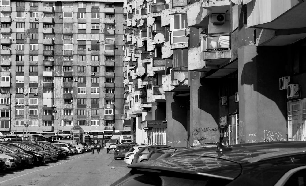 grayscale photo of cars parked on street