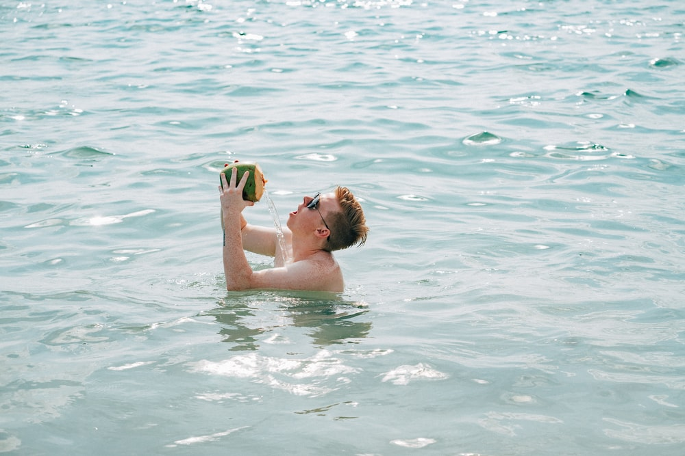 woman in swimming goggles on water during daytime