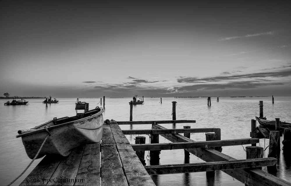 white and black boat on sea dock during daytime