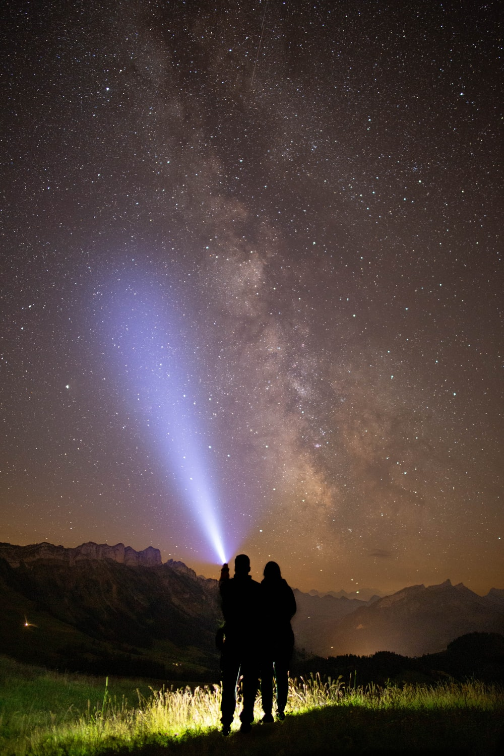 silhouette of 2 person sitting on rock under starry night