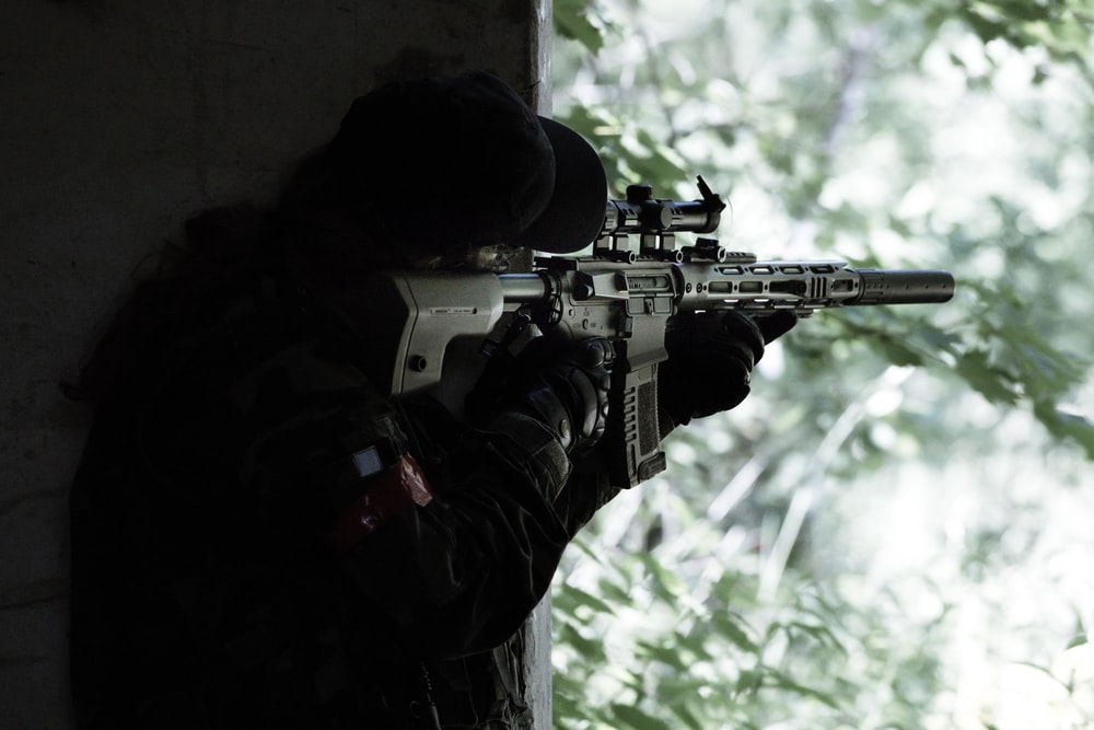 man in black jacket holding black rifle