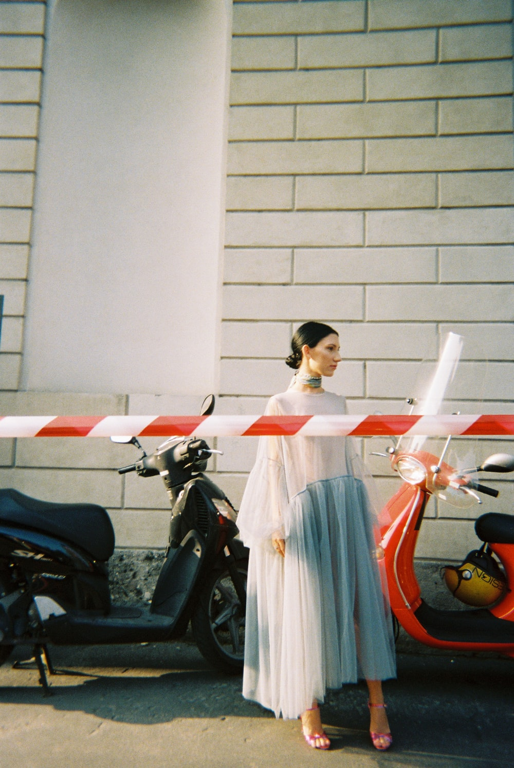 woman in white and red dress standing beside black motorcycle
