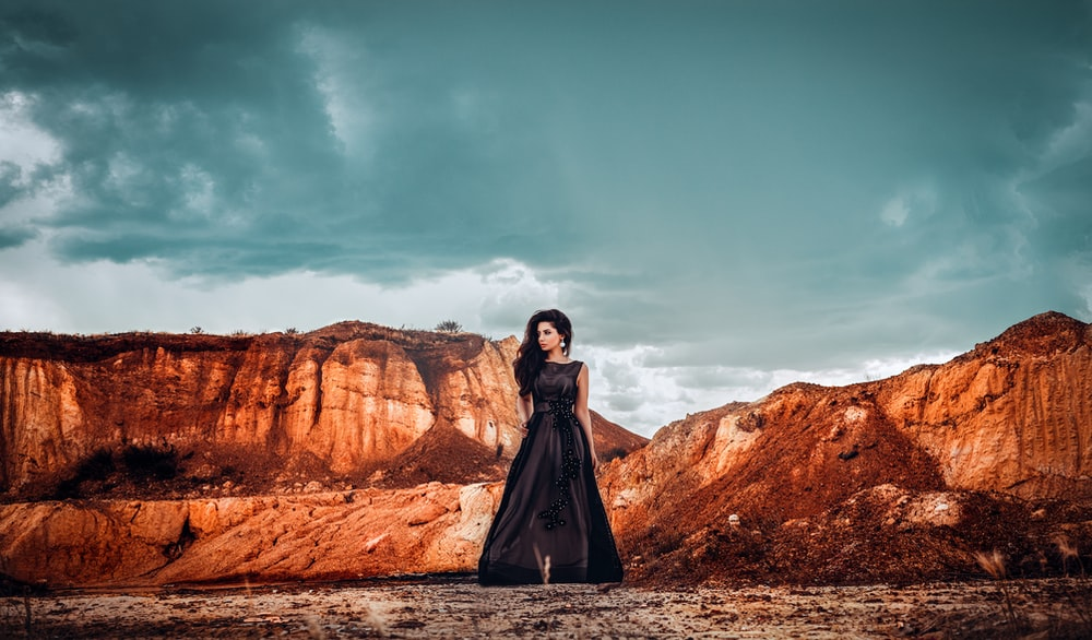 woman in black dress standing on brown rock formation under blue sky during daytime