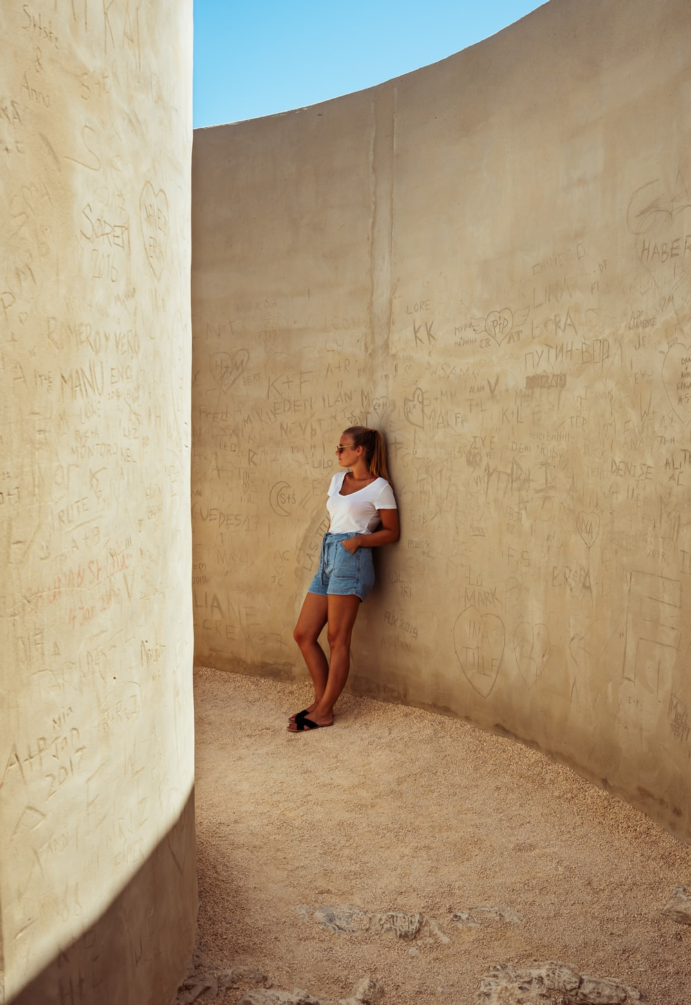 girl in white t-shirt and blue denim shorts leaning on beige wall