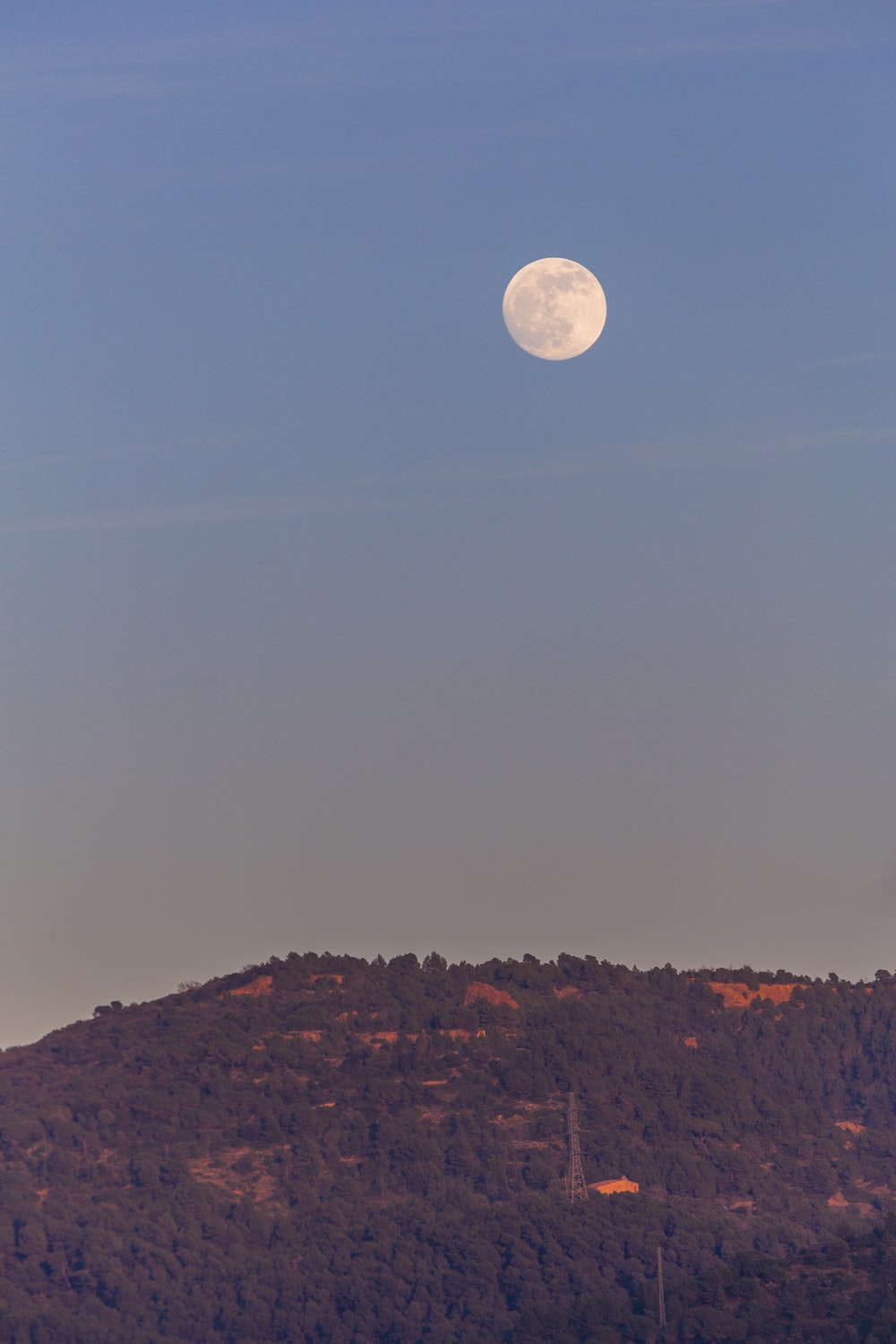 full moon over brown mountain