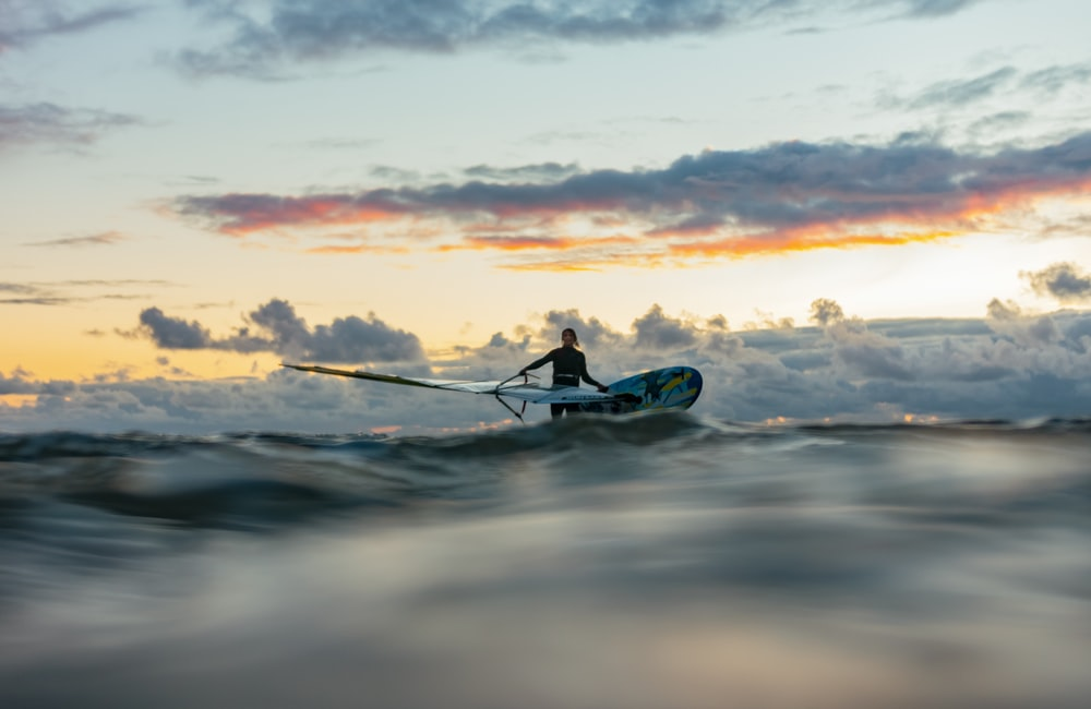 silhouette of man riding on blue kayak on sea during sunset