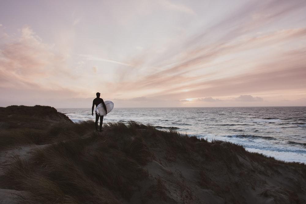 man in black shirt and pants walking on seashore during daytime