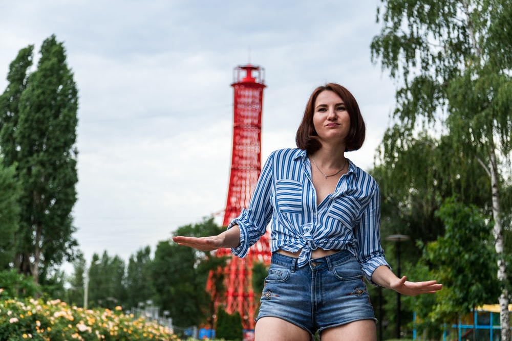 woman in blue and white striped button up shirt and blue denim shorts standing on yellow