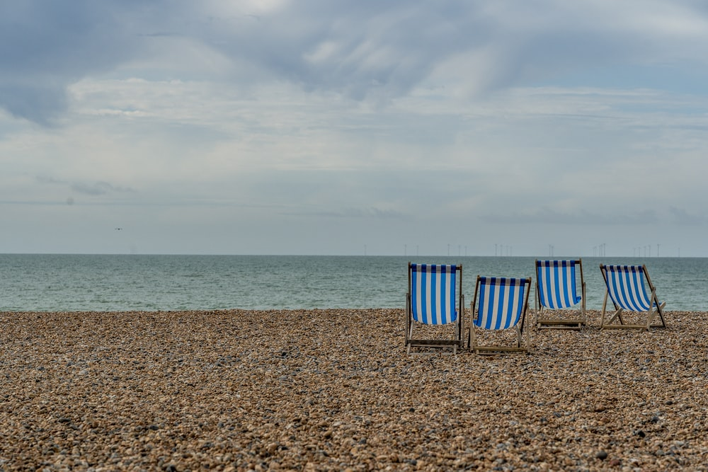 blue and white beach chairs on beach during daytime
