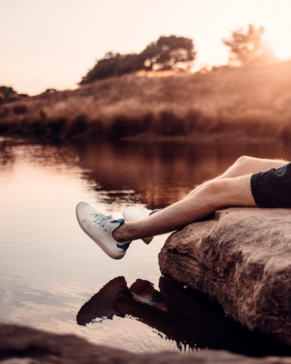 person wearing white sneakers sitting on brown rock near body of water during sunset