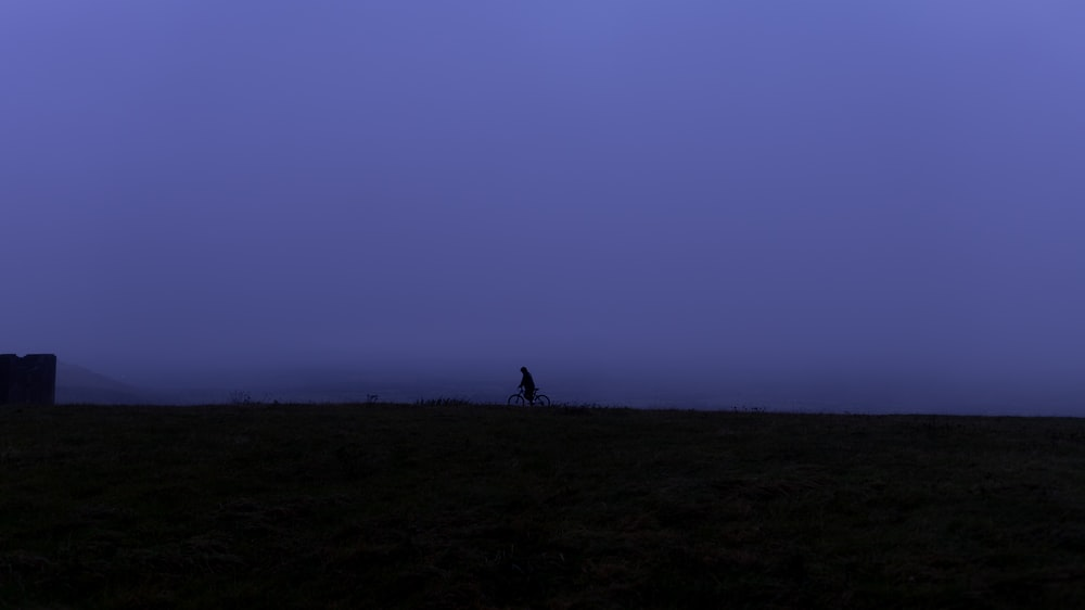 silhouette of person standing on hill during daytime