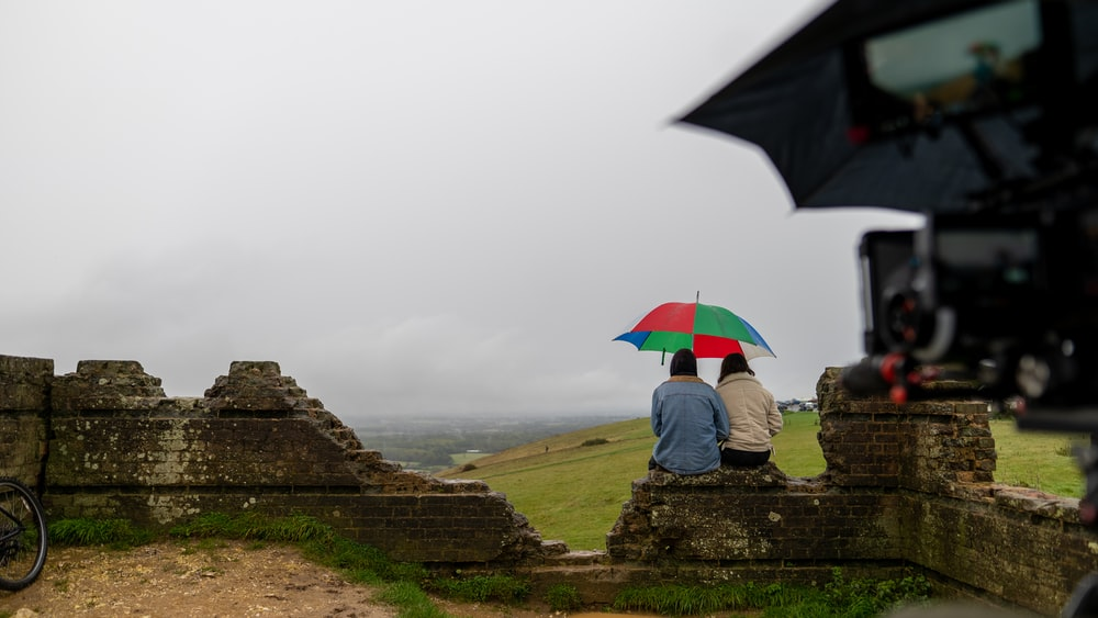 person sitting on rock near red umbrella during foggy weather