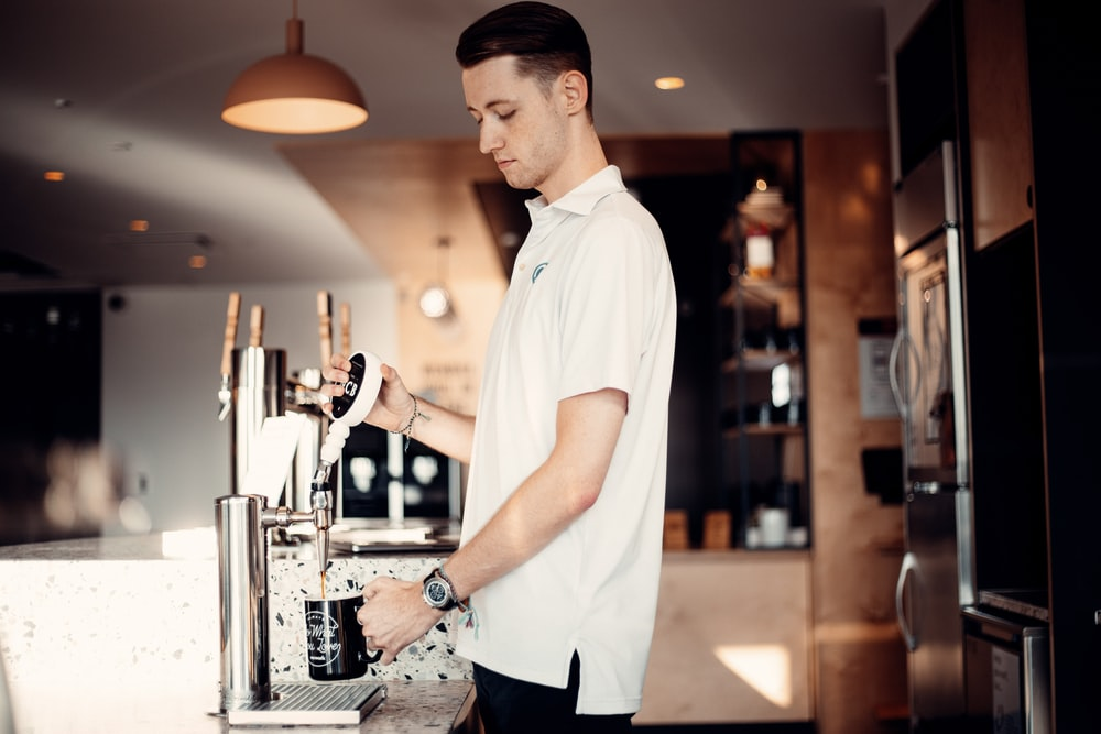 man in white button up t-shirt and black pants standing in front of espresso machine