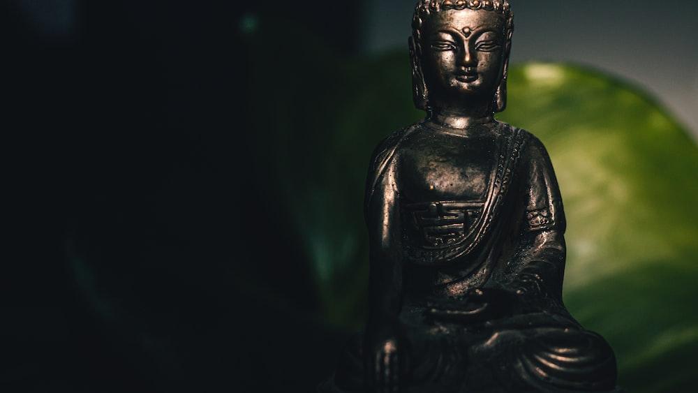 black buddha statue in black background