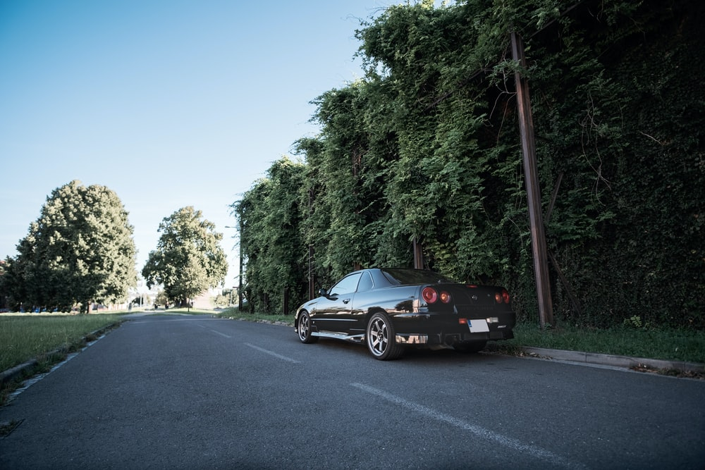 black coupe on road near green trees during daytime