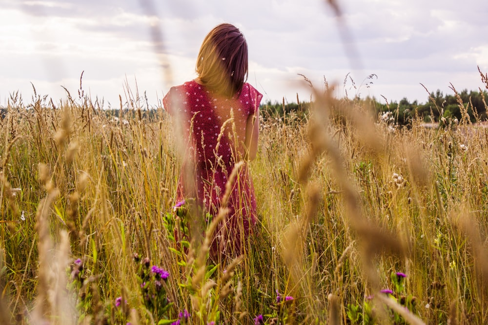 woman in pink dress standing on green grass field during daytime