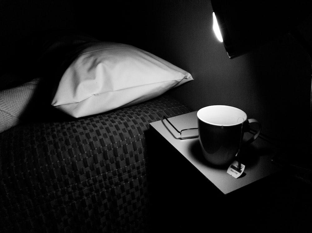 white ceramic mug on black and white textile