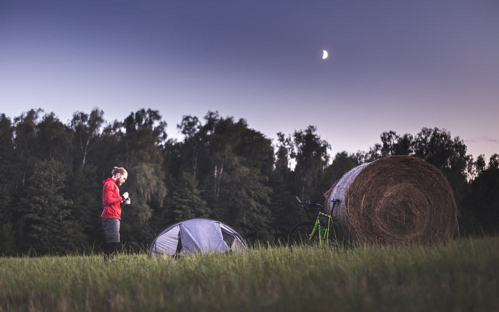 woman in red jacket standing beside white dome tent during night time