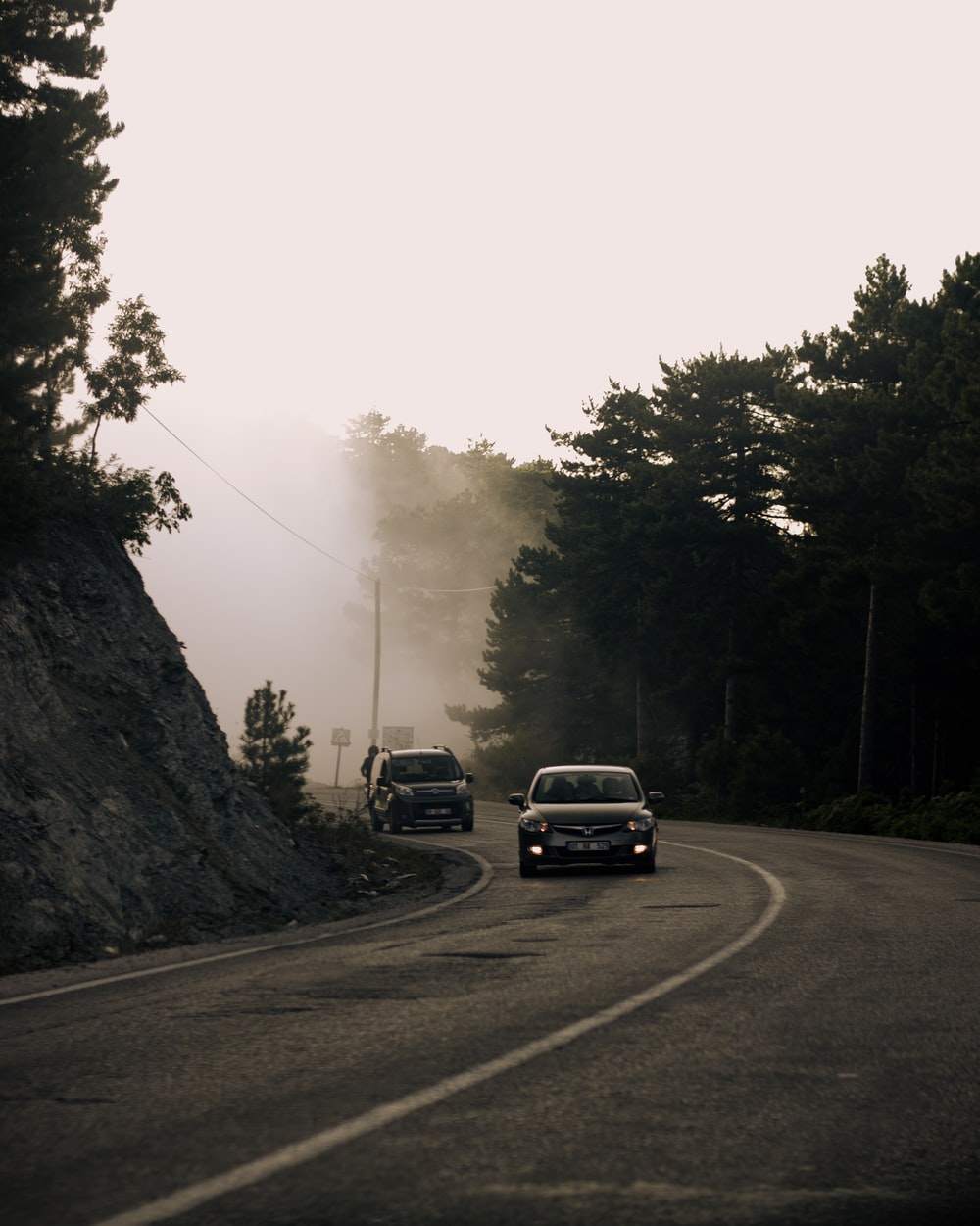 black suv on road near trees during daytime