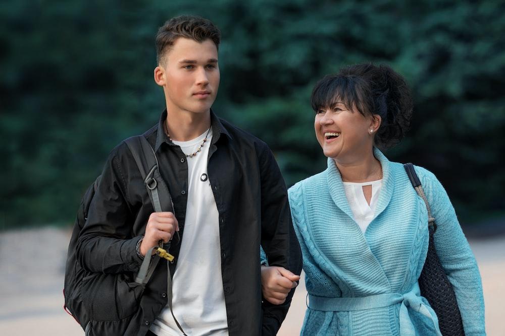 man in blue v neck shirt and black jacket standing beside woman in blue v neck