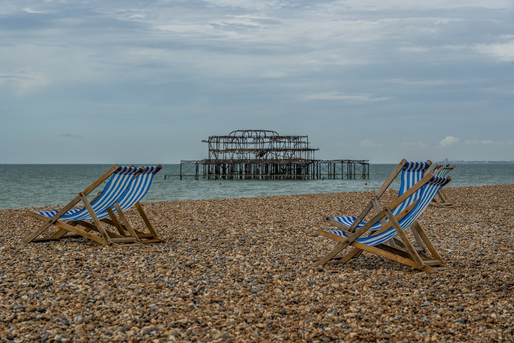 brown wooden folding chairs on beach during daytime