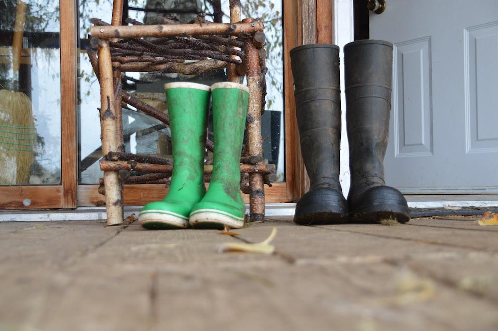 green rain boots on brown wooden ladder