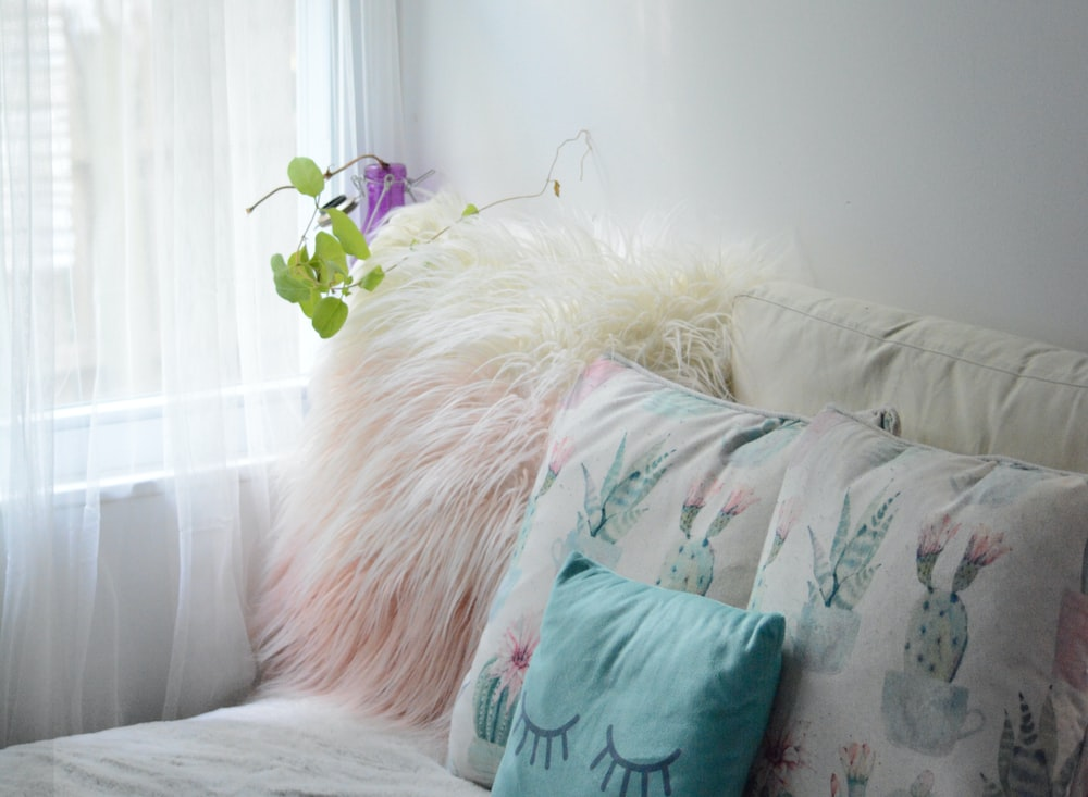 green throw pillow on white couch