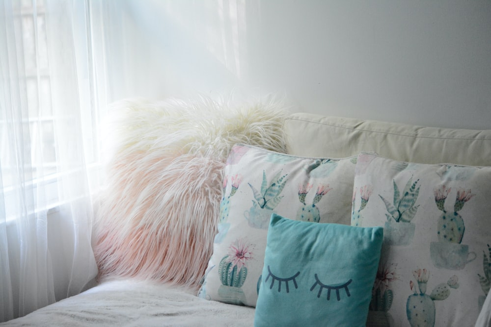 green throw pillow on white bed
