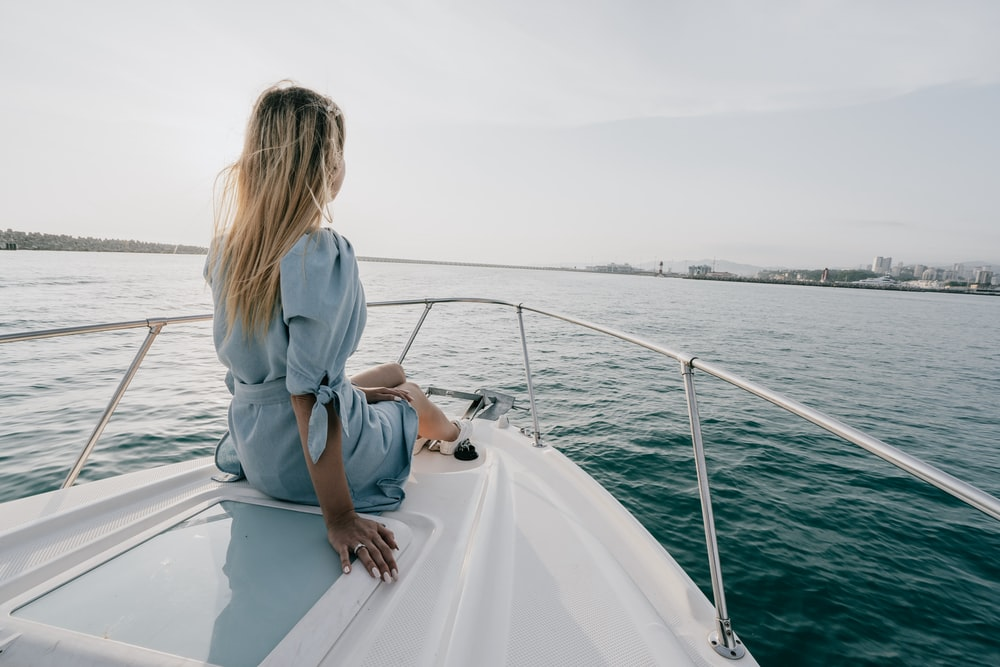 woman in white long sleeve shirt sitting on white boat during daytime