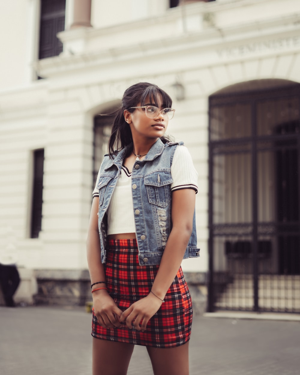 woman in blue denim button up jacket and red and black plaid skirt standing on sidewalk
