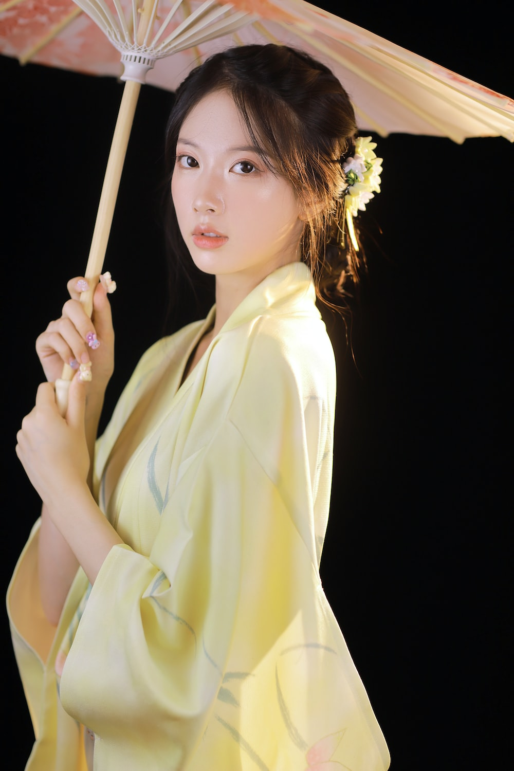 woman in yellow robe holding brown wooden stick