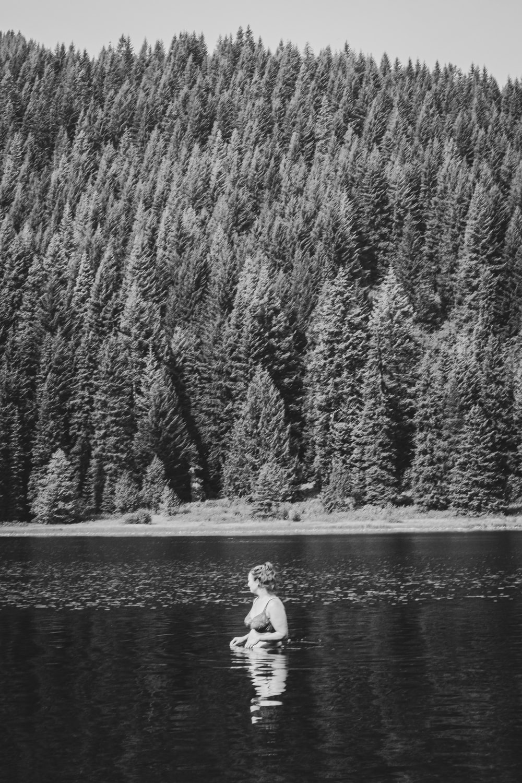 woman in white long sleeve shirt standing near lake