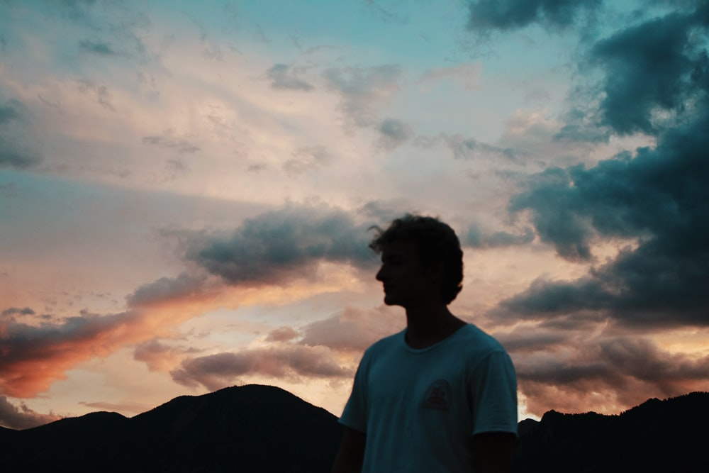 man in white crew neck t-shirt standing on mountain under white clouds during daytime