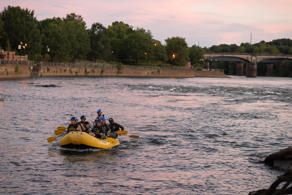 2 people riding yellow kayak on body of water during daytime