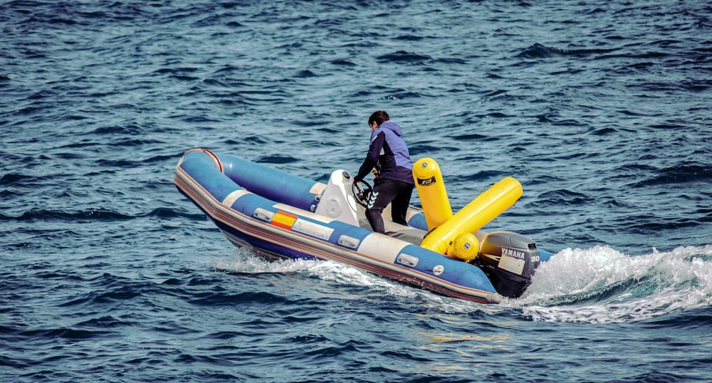 man in black jacket riding on orange and white inflatable boat during daytime