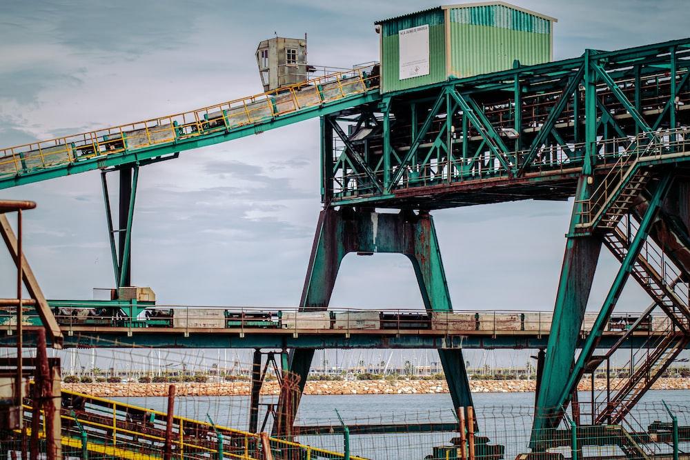 green and brown metal bridge under blue sky during daytime