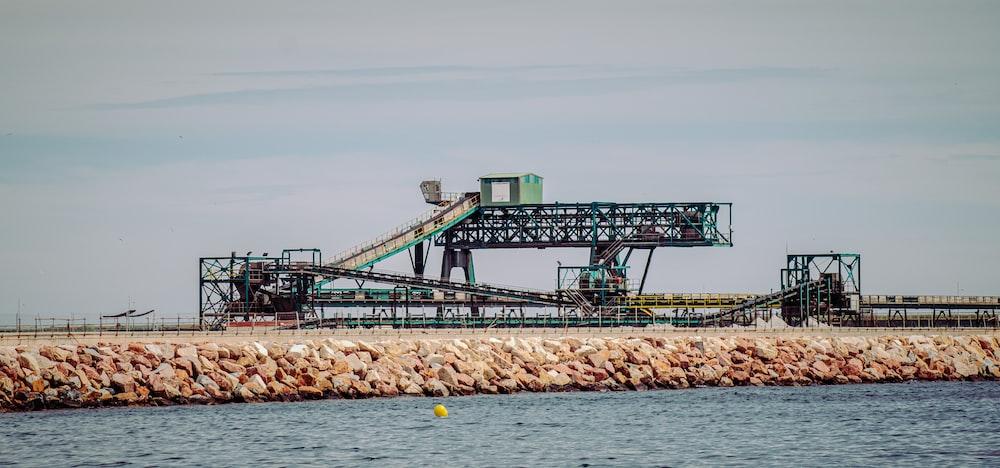 green and white metal bridge over the sea