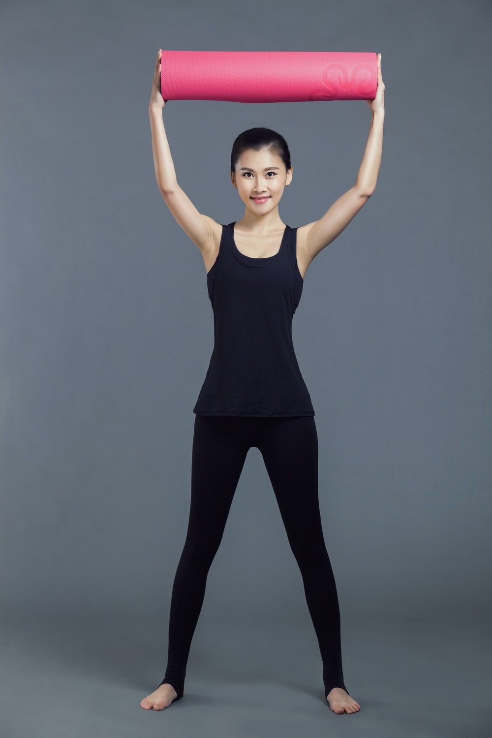 woman in black tank top and blue pants raising her right hand