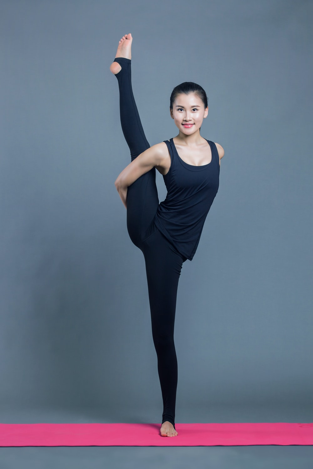 woman in black tank top and black pants raising her right hand