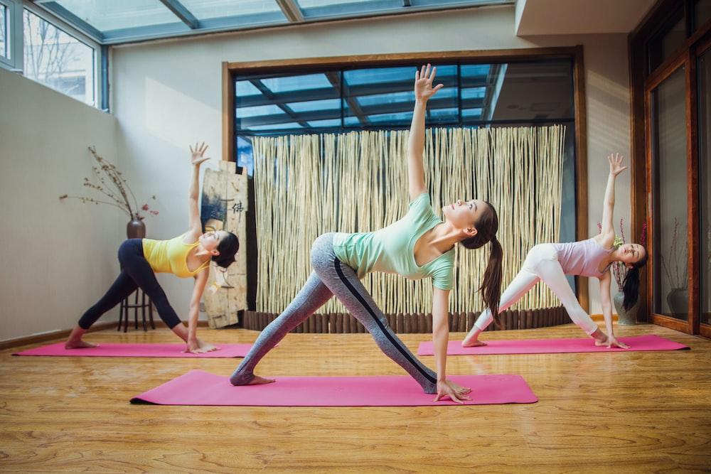 woman in gray tank top and gray leggings doing yoga