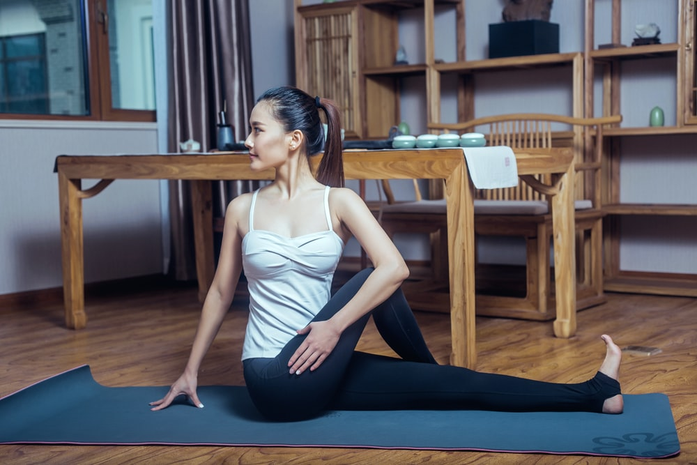 woman in white tank top and black pants sitting on blue yoga mat
