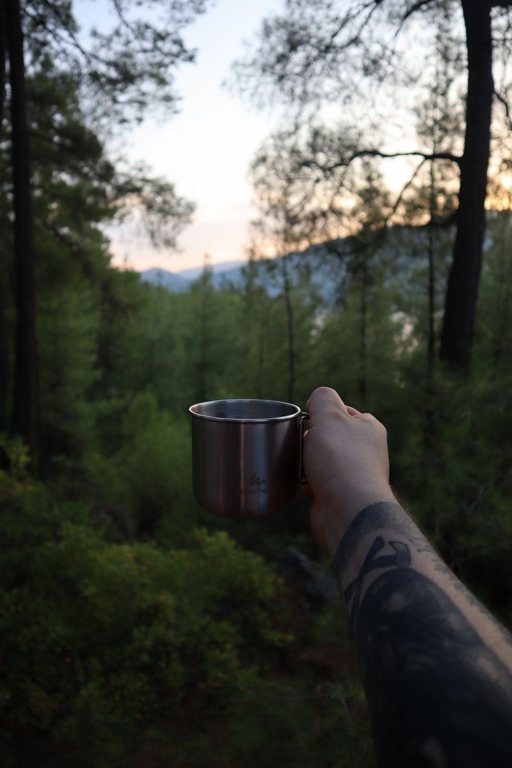 person holding stainless steel cup