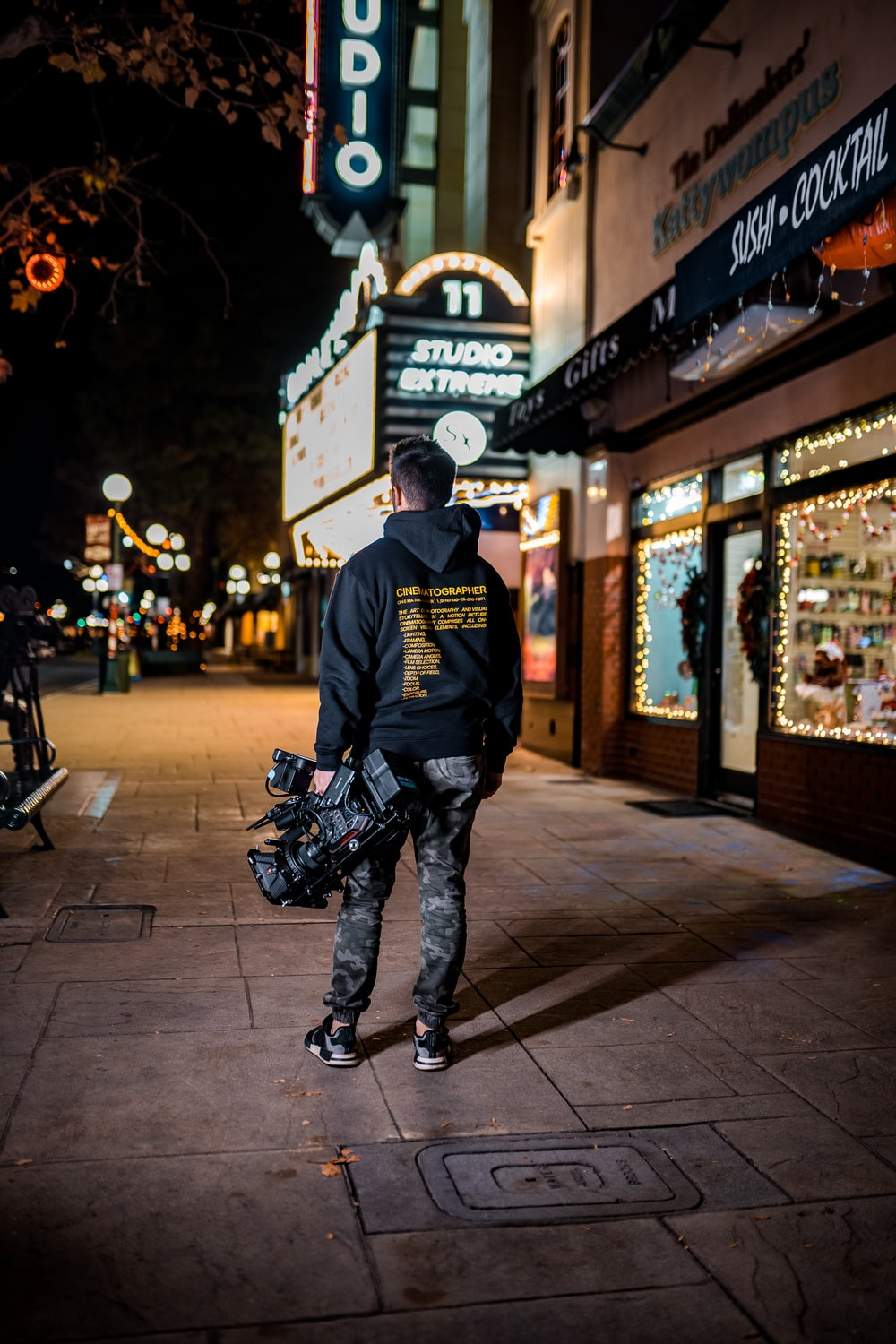 man in black long sleeve shirt and black pants standing on sidewalk during night time