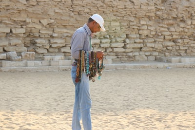 man in white thobe standing on sand during daytime cairo teams background
