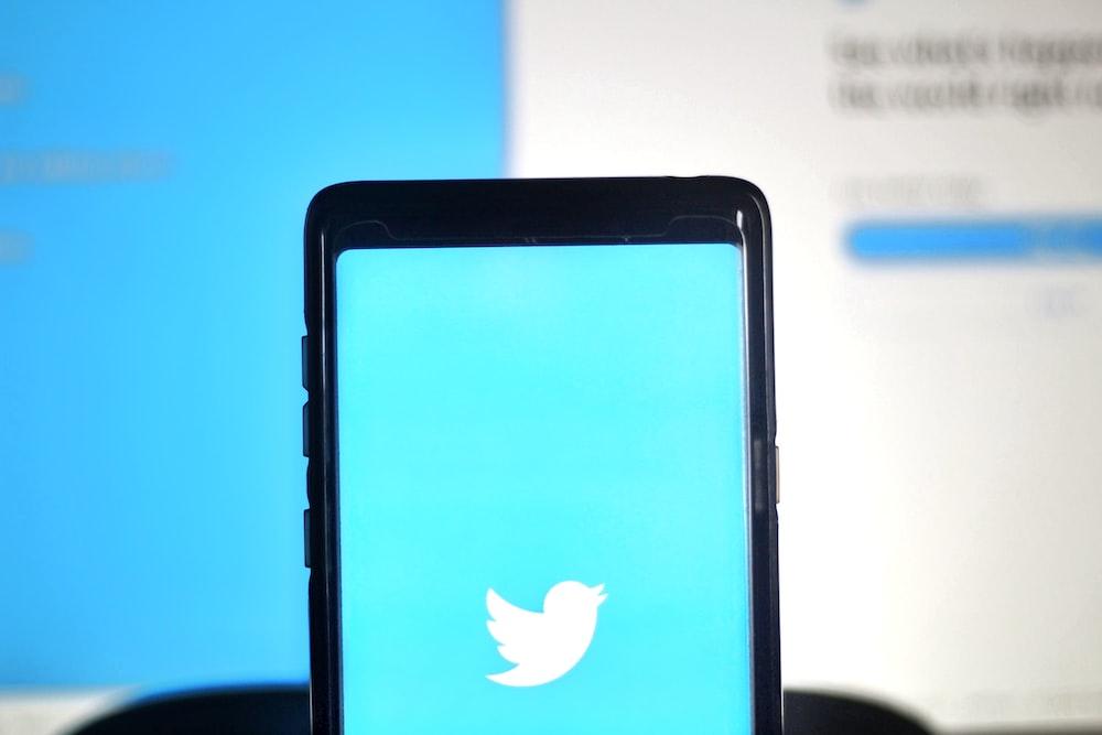 black smartphone on blue surface